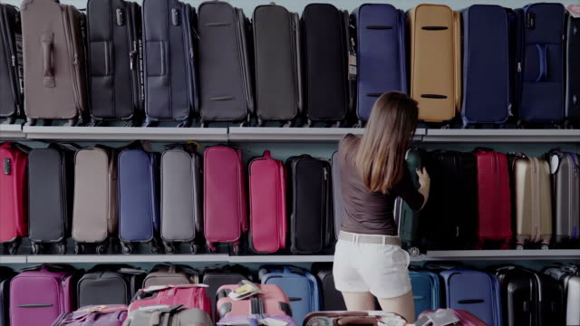 Woman chooses suitcase at shop video