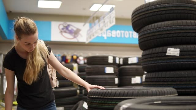 Woman chooses tires for car. Woman is choosing new tires for her car in autoshop. Female car driver looking for new tires in the store. Shopping for the car. tires stock videos & royalty-free footage