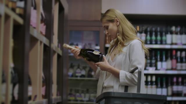 vídeos y material grabado en eventos de stock de mujer elige vino en el supermercado, el cliente selecciona el producto en los estantes de la tienda en. venta de alcohol. lea la etiqueta en la botella de vino - eventos de etiqueta