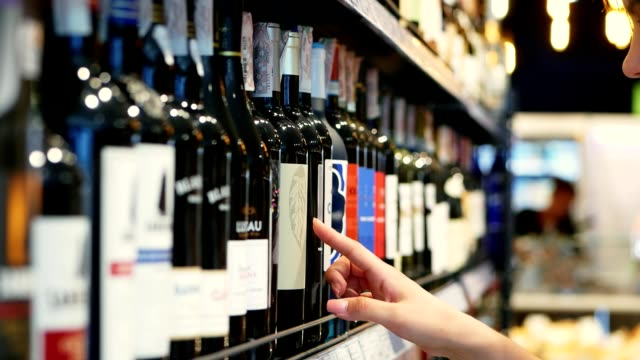 Woman chooses wine in the Supermarket, customer selects product on the shelves in the store in close-up