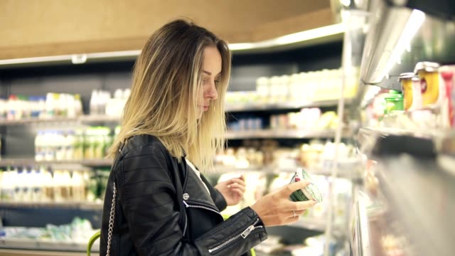 vídeos de stock e filmes b-roll de woman chooses yogurt in the supermarket. blonde woman choosing products in shopping mall. girl stands near the store shelf and selects the products - prateleira compras