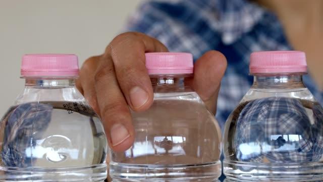vídeos de stock, filmes e b-roll de mulher escolhendo uma garrafa de água - garrafa