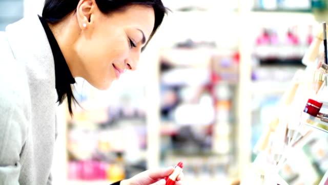 Woman choosing a lipstick at beauty store. video