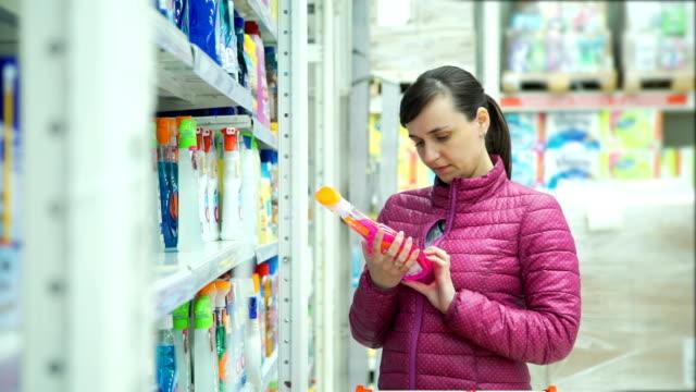 frau wählt einen fensterputzer beim supermarkt - etikett stock-videos und b-roll-filmmaterial