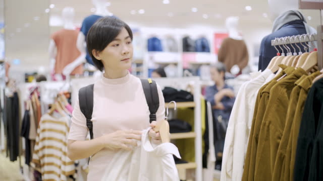 Woman choosing clothes and looking to mirror in clothing store video
