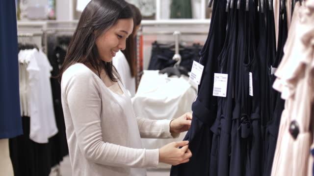 vídeos de stock, filmes e b-roll de mulher escolhendo roupas em uma loja de roupas - shopping center