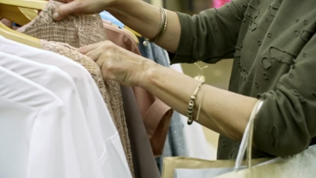 Woman Choosing Clothes in Shopping Mall video