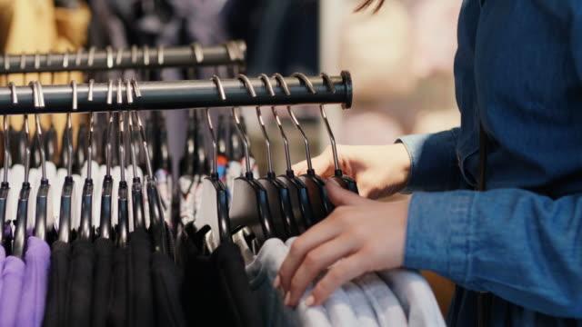 vídeos y material grabado en eventos de stock de mujer eligiendo ropa en el estante - vestimenta