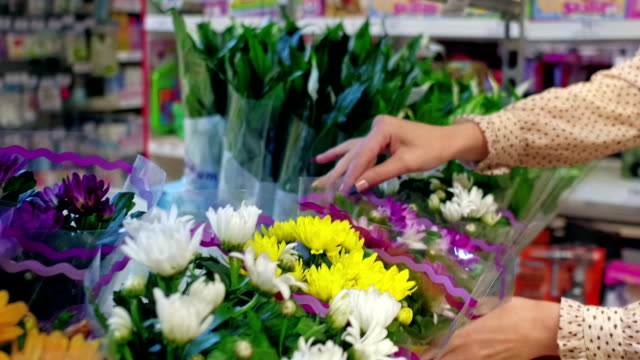 Woman choosing flowers in the shop video