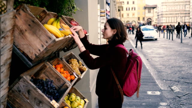 Woman choosing fresh fruits on the street of Florence video