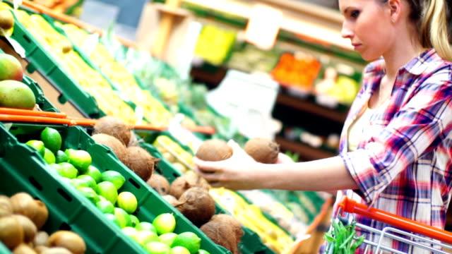 Mujer en el supermercado elegir frutas. - vídeo
