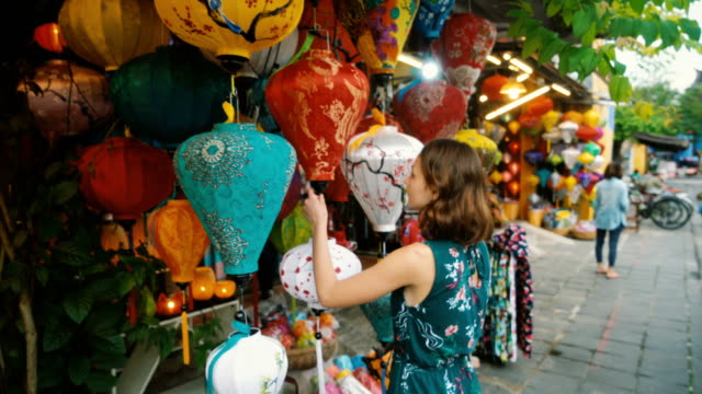 woman choosing lanterns in hoi an - prodotto d'artigianato video stock e b–roll
