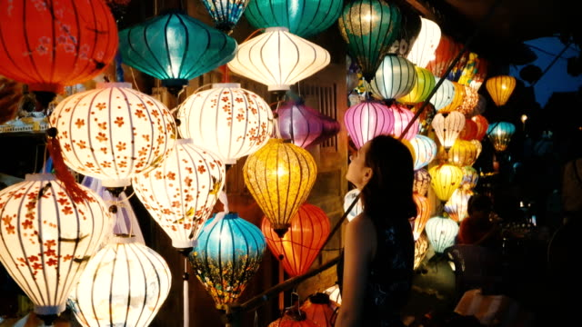 woman choosing lanterns in hoi an - lanterna attrezzatura per illuminazione video stock e b–roll