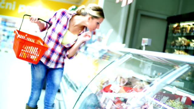 Woman choosing meat products at supermarket. video