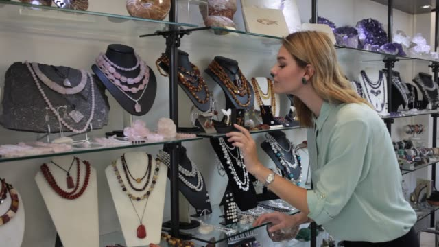 woman choosing natural stone beads necklace in shop - paragone video stock e b–roll