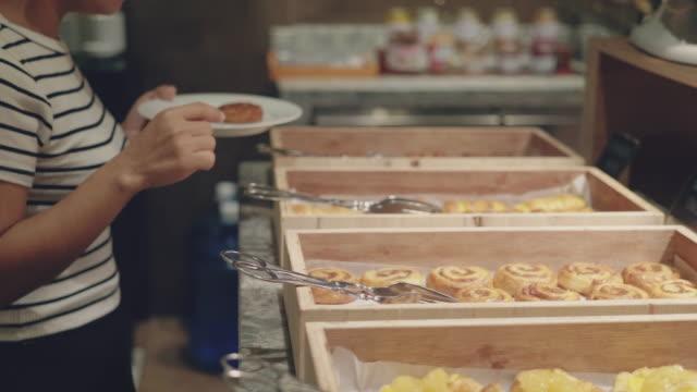 woman choosing pastry for her breakfast - buffet video stock e b–roll