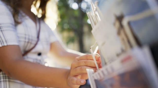 vidéos et rushes de femme choisissant des cartes postales sur la rue - carte postale