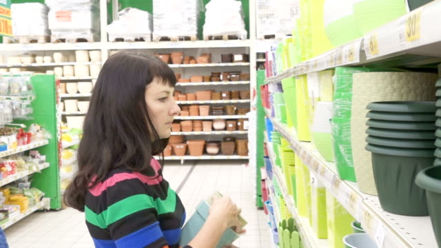 Woman choosing pot for flowers in shop. Woman in a supermarket. The girl in the shop. Buyer. Choose plants. Buy houseplants. Flower shop video