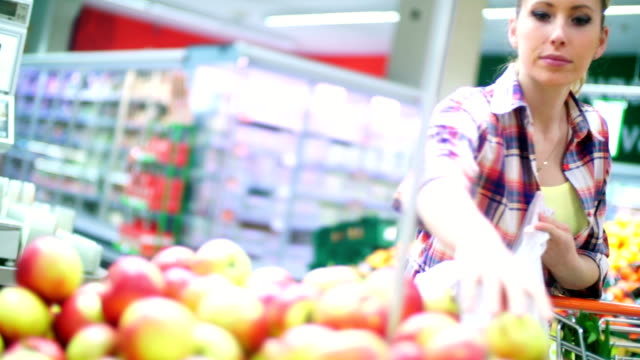 Woman choosing some apples in supermarket. video