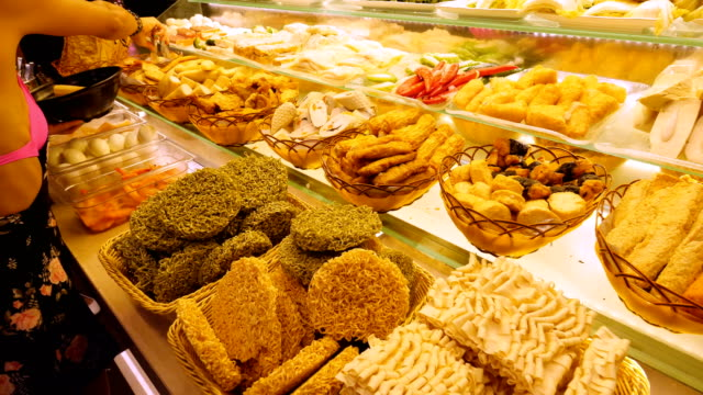 woman choosing some asia food from a buffet in singapore - buffet video stock e b–roll