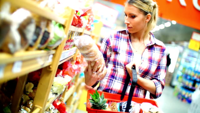 Woman choosing some food in supermarket. Closeup of late 20's attractive blond woman choosing some food products in a supermarket. She's next to arranged stack of unrecognizable products and taking a loaf of bread. Carrying red shopping basket. bread stock videos & royalty-free footage