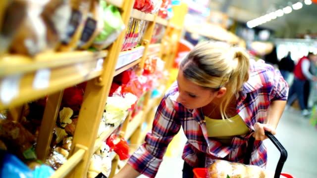vidéos et rushes de femme dans un supermarché choisir une nourriture. - décolleté