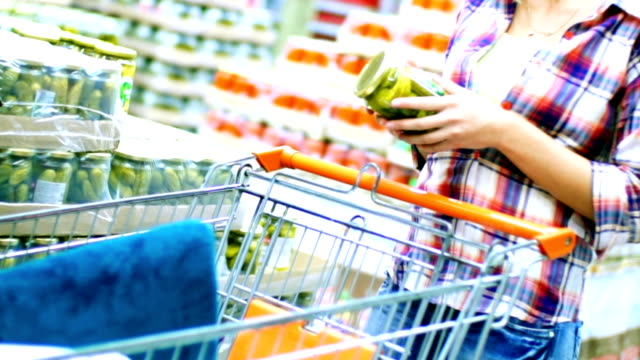 Woman choosing some food in supermarket. Closeup of late 20's attractive blond woman choosing  food products in a supermarket. She's next to arranged stack of unrecognizable products and taking some bottles and jars. Pushing red shopping cart. pickle stock videos & royalty-free footage