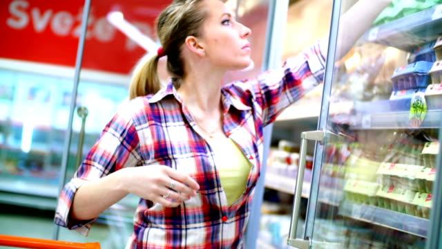 Woman choosing some food in supermarket. video