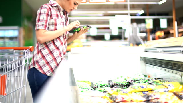 Woman choosing some food in supermarket. Closeup of late 20's attractive blond woman choosing some frozen food in a supermarket. She's next to large freezer and putting some items into her basket. Carrying red shopping basket. Side view, HD video. frozen stock videos & royalty-free footage