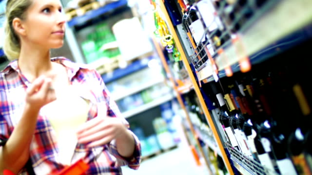 Woman choosing some wine in supermarket. video