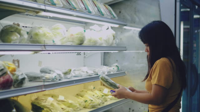 woman choosing vegetables at supermarket - paragone video stock e b–roll