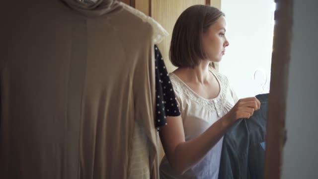 Woman choosing what to wear in her wardrobe holding a dress on coathanger Woman choosing what to wear coathanger stock videos & royalty-free footage