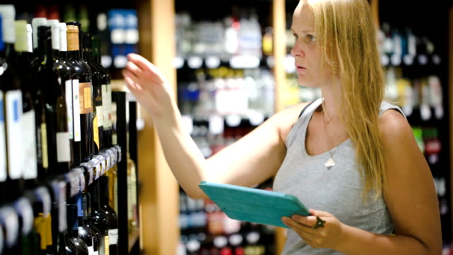 Woman choosing wine using pad video