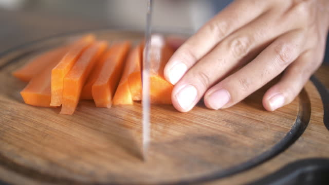 SLO MO Woman chopping carrots in kitchen video