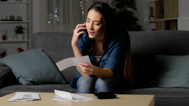 Woman claiming wrong receipt on phone Relaxed woman claiming wrong receipt on phone sitting on a couch in the night at home financial bill stock videos & royalty-free footage