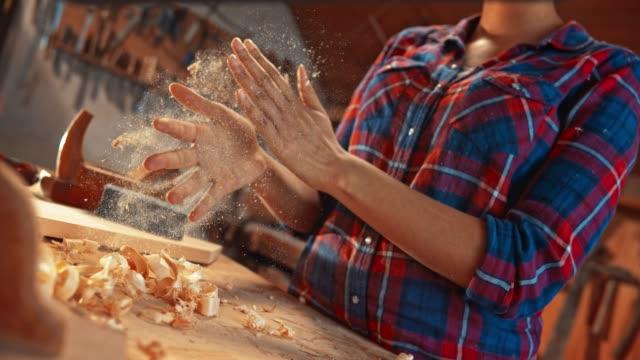 slo mo ld woman klatschen die hände in der werkstatt, um holzstaub von den händen zu bekommen - schnitzen stock-videos und b-roll-filmmaterial