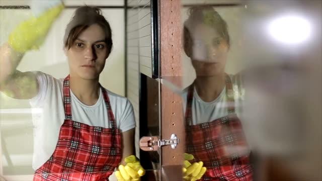 donna che pulisce un vetro sulla finestra - addetto alle pulizie video stock e b–roll