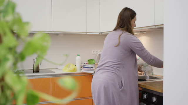 vídeos de stock e filmes b-roll de woman cleaning and recycling trash from the kitchen - economia circular
