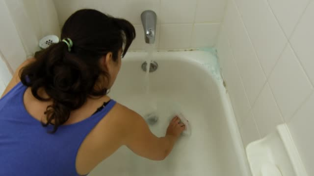 Woman cleaning and scrubbing bathtub with a brush during quarantine video