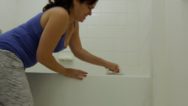Woman cleaning bathtub with a brush during quarantine video
