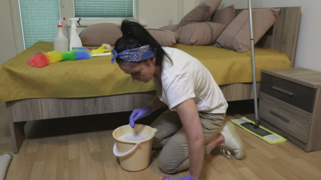 Woman cleaning floor by wet rag at home - vídeo