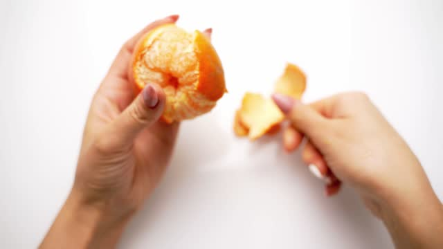 Woman cleans tangerine on the table.
