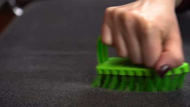 A woman cleans the fabric from dirt with a large brush. Green brush in a woman's hand close-up.