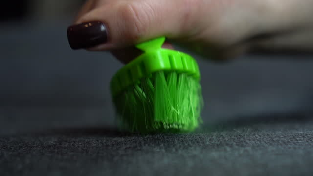 A woman cleans the fabric from dirt with a large brush. Green brush in a woman's hand close-up. Slow motion.