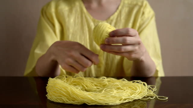 Woman clewing up the yellow yarn up video