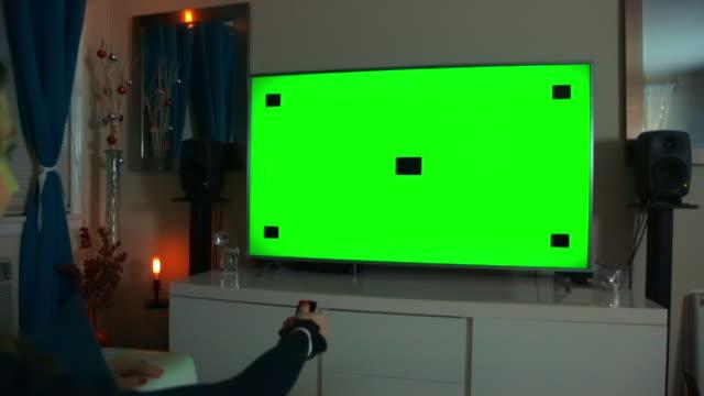 woman clicking remote button - tv green screen - night - dolly shot - carrellata video stock e b–roll