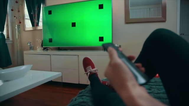 Woman Clicking Remote Button, TV Green-Screen Medium Dolly Shot of a caucasian woman sitting comfortably in her living room, watching TV, and uses a remote to press a button. TV screen is set on green screen with tracking marks. changing channels stock videos & royalty-free footage