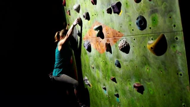 ein frau kletterer ist ausgebildet, um hindernisse auf der wand für kletterer zu überwinden. professionelle helfer. slow-motion - bouldering stock-videos und b-roll-filmmaterial