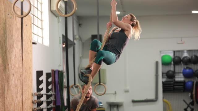 woman climbing a rope - napinać mięśnie filmów i materiałów b-roll