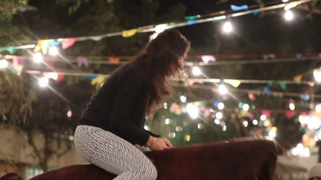 Woman climbing on to mechanical bull. Girl rides electric mechanical bull